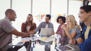 Happy young business team working together at creative office desk